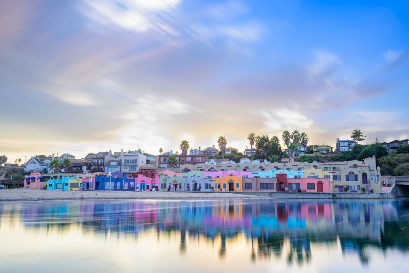 A row of multicolored pastel houses right in front of a body of water before sunset.