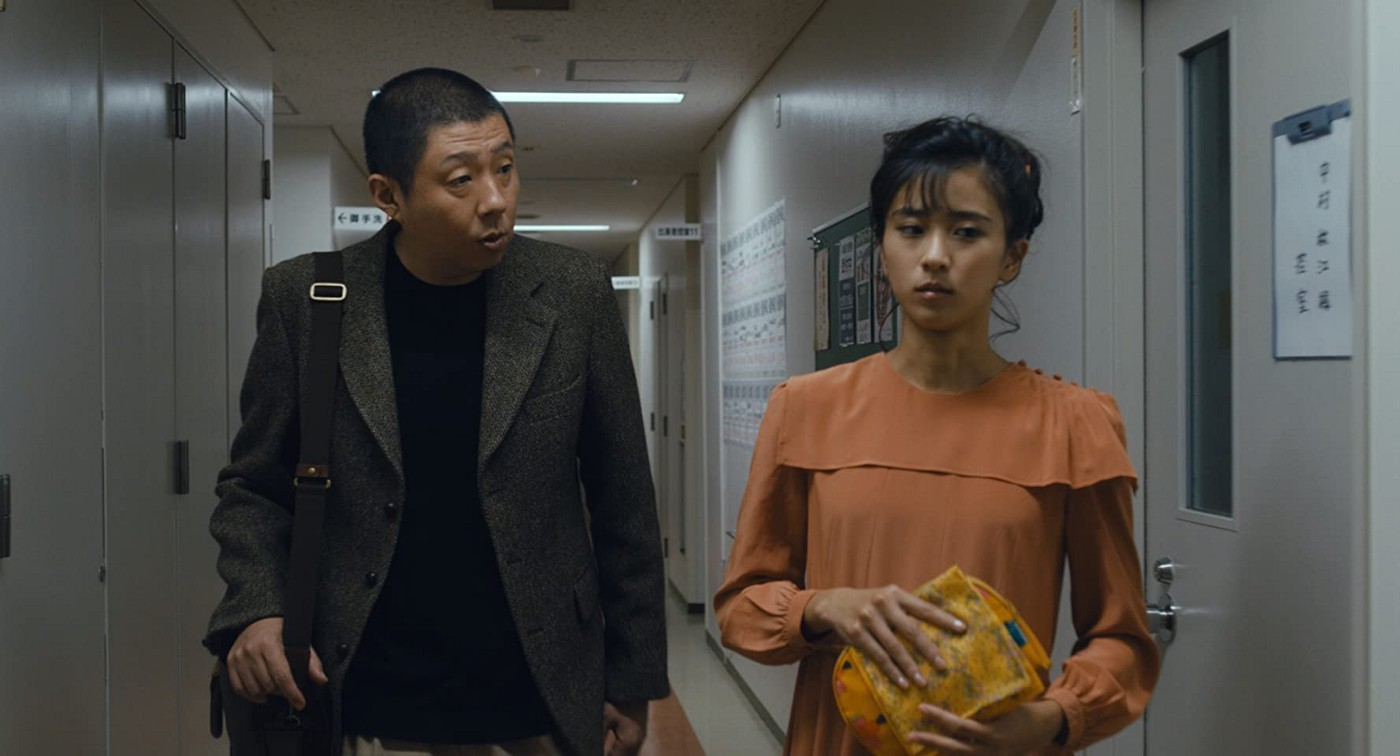 In 'JU-ON: Origins', Yasuo is explaining his findings while Haruka looks to the right, seemingly in thought.