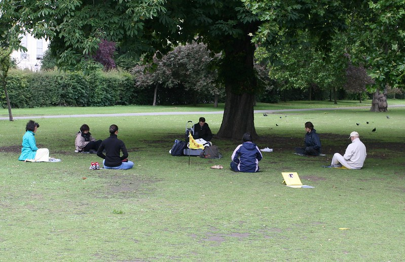 A circle of seven people sit in meditation in Regents Park, London.