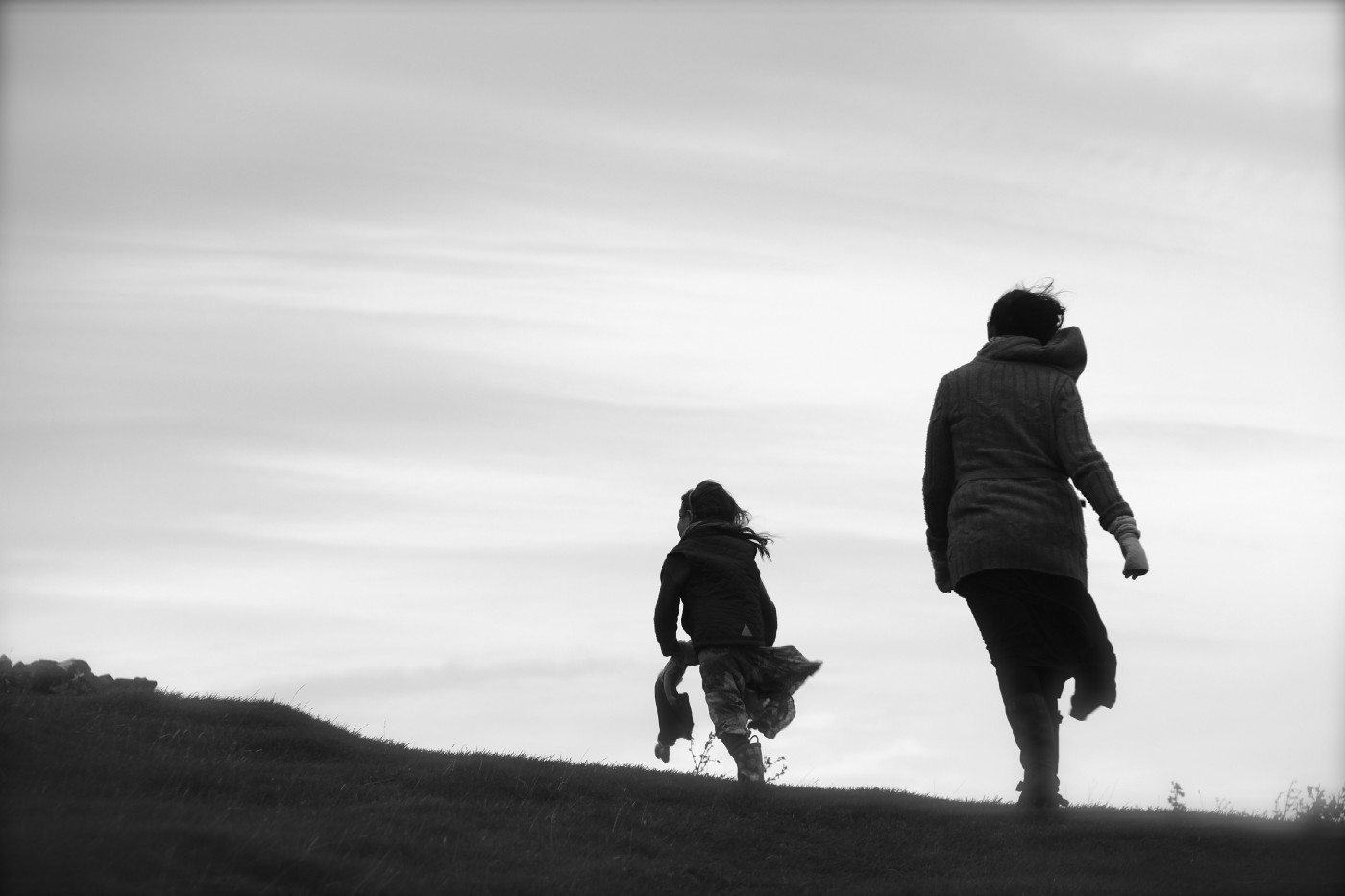 Black and white image of mother and daughter walking away over craggy hill.