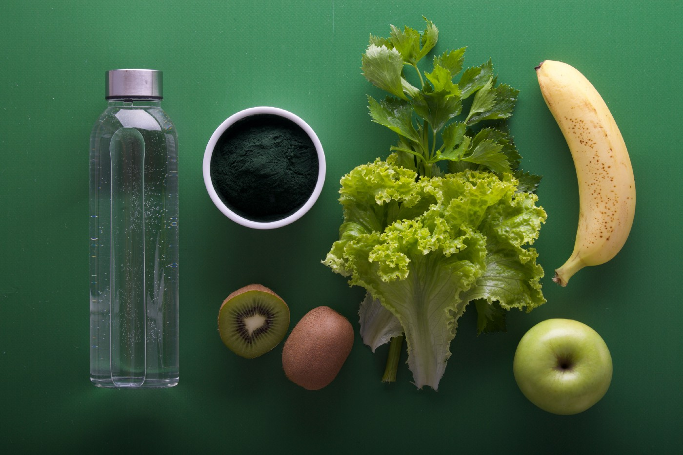Assortment of green veg, a kiwi, water bottle, apple and banana on a green background