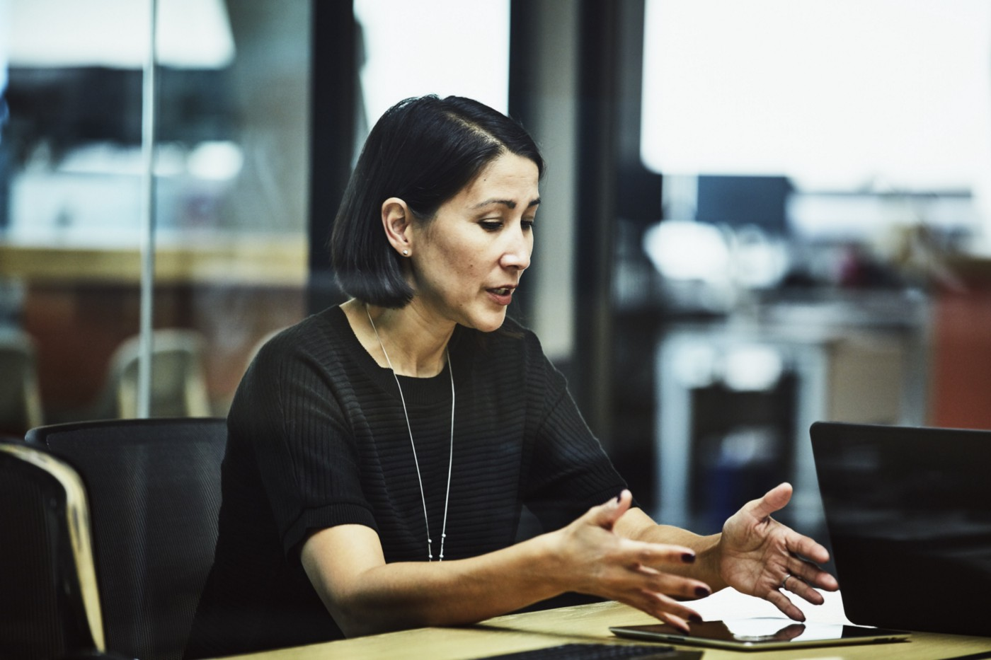 A photo of a woman in a work meeting.
