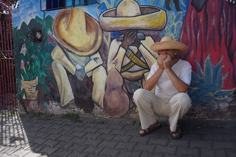 Author playing harmonica crouched in front of a mural of musicians dressed the same way: all white, broad-brimmed hat.