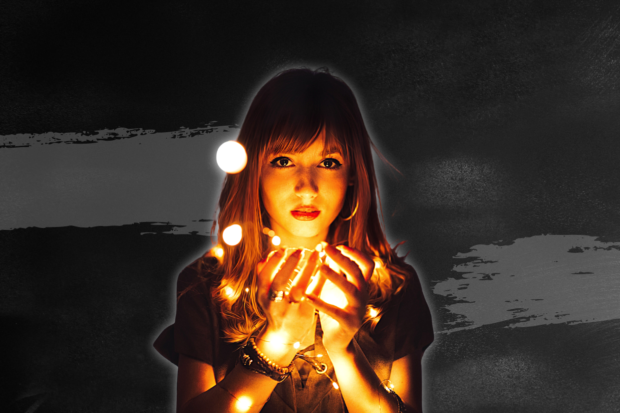 Young woman holding light between her hands