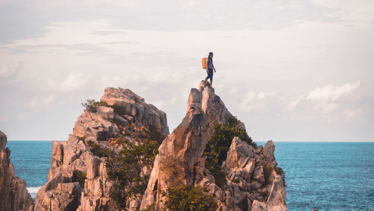 Man standing on rock at sea