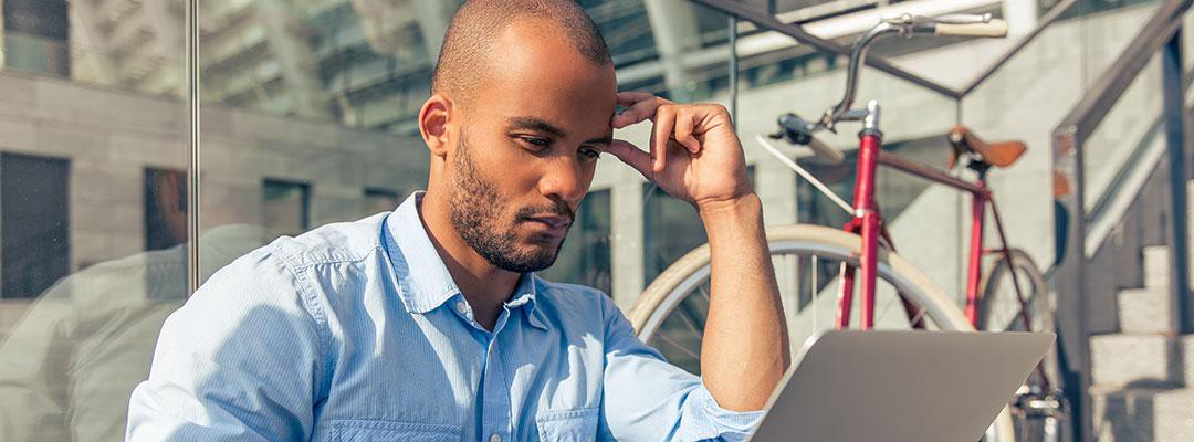 Black male professional wearing a blue-collar shirt working on a laptop