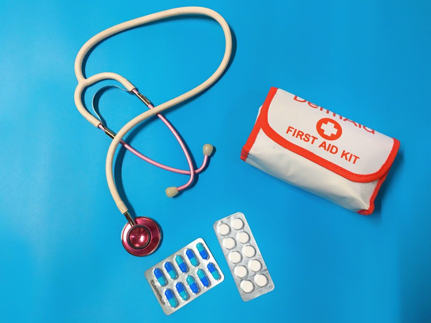 A stethoscope, blood pressure cuff, and two blister packs of pills.