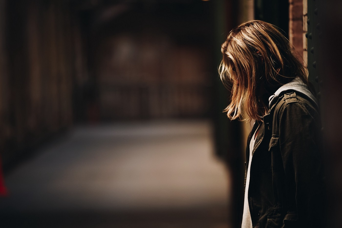 woman leaning against wall facing down & depressed