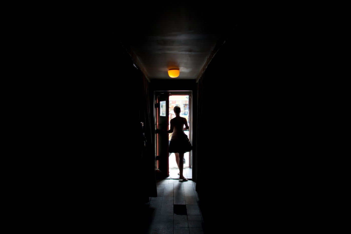 A mostly dark photo of a woman who is opening a door that casts light in the middle of the picture.