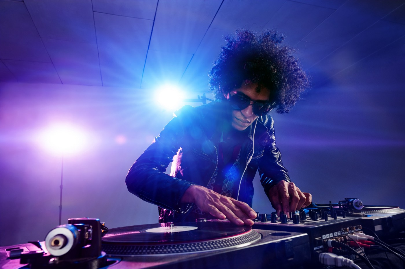 Cool DJ with sunglasses, silhouetted by strobe light, over turntable, intently trying to connect to the crowd with his music