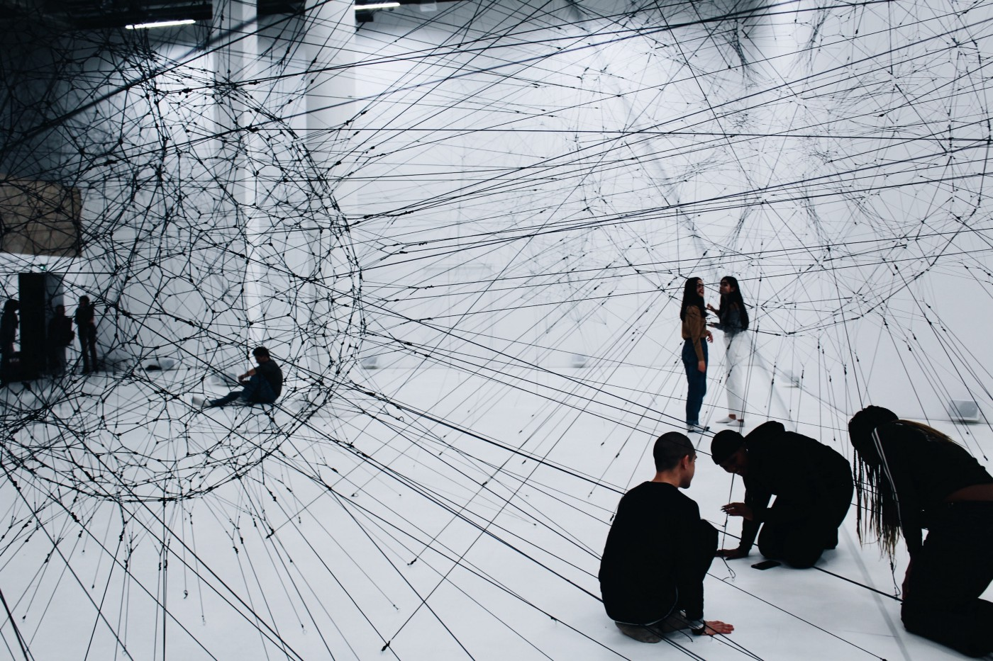 An image of a group of people working on the floor, with an overlaid image of circles and lines representing a network.