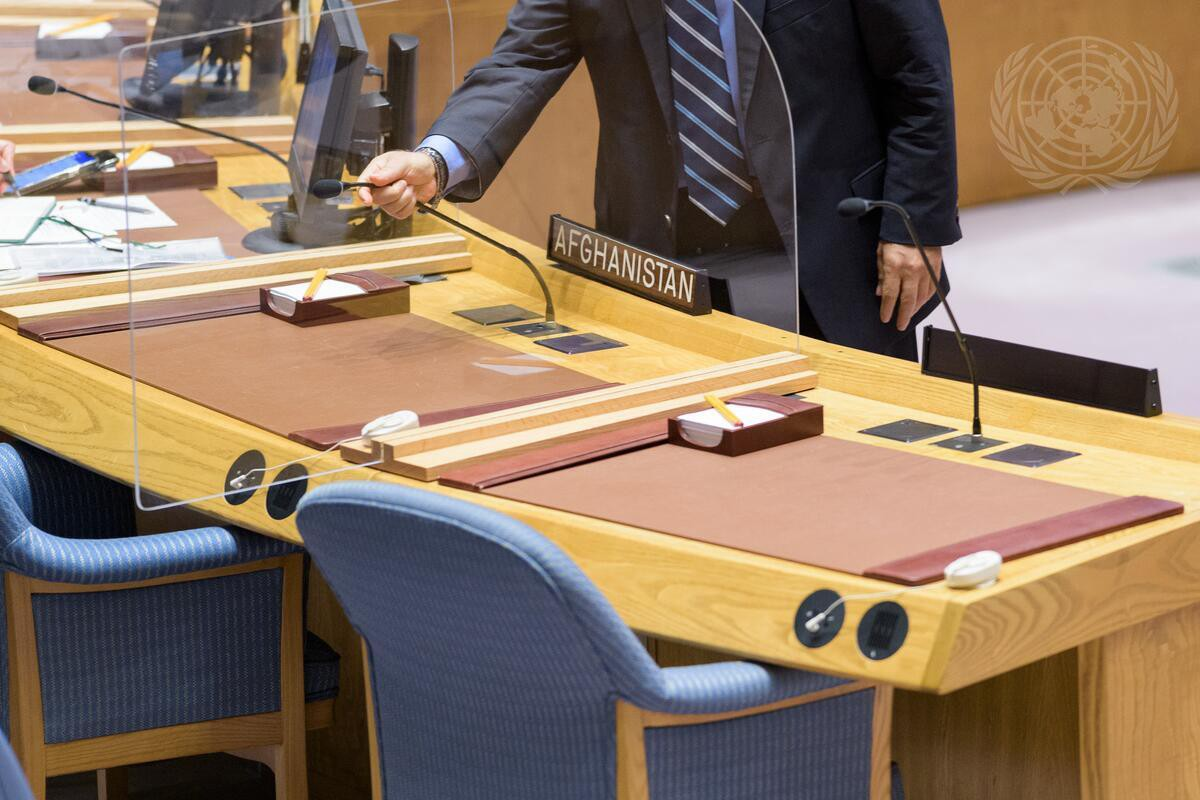 A conference officer adjusts the microphone ahead of the Security Council meeting on the situation in Afghanistan.