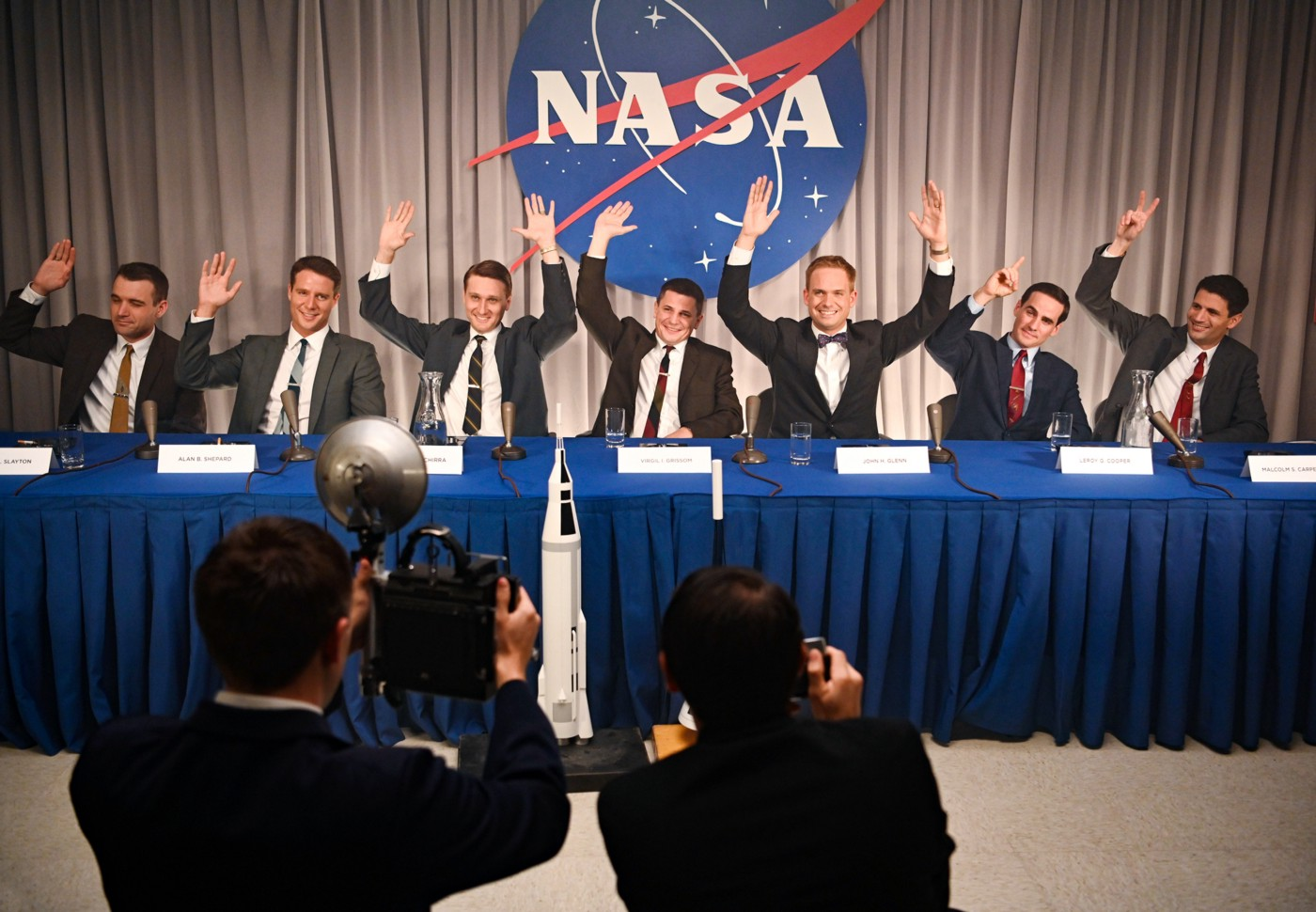 A group of men in suits at a long table at a press conference, raising their hands while photographers take their picture.