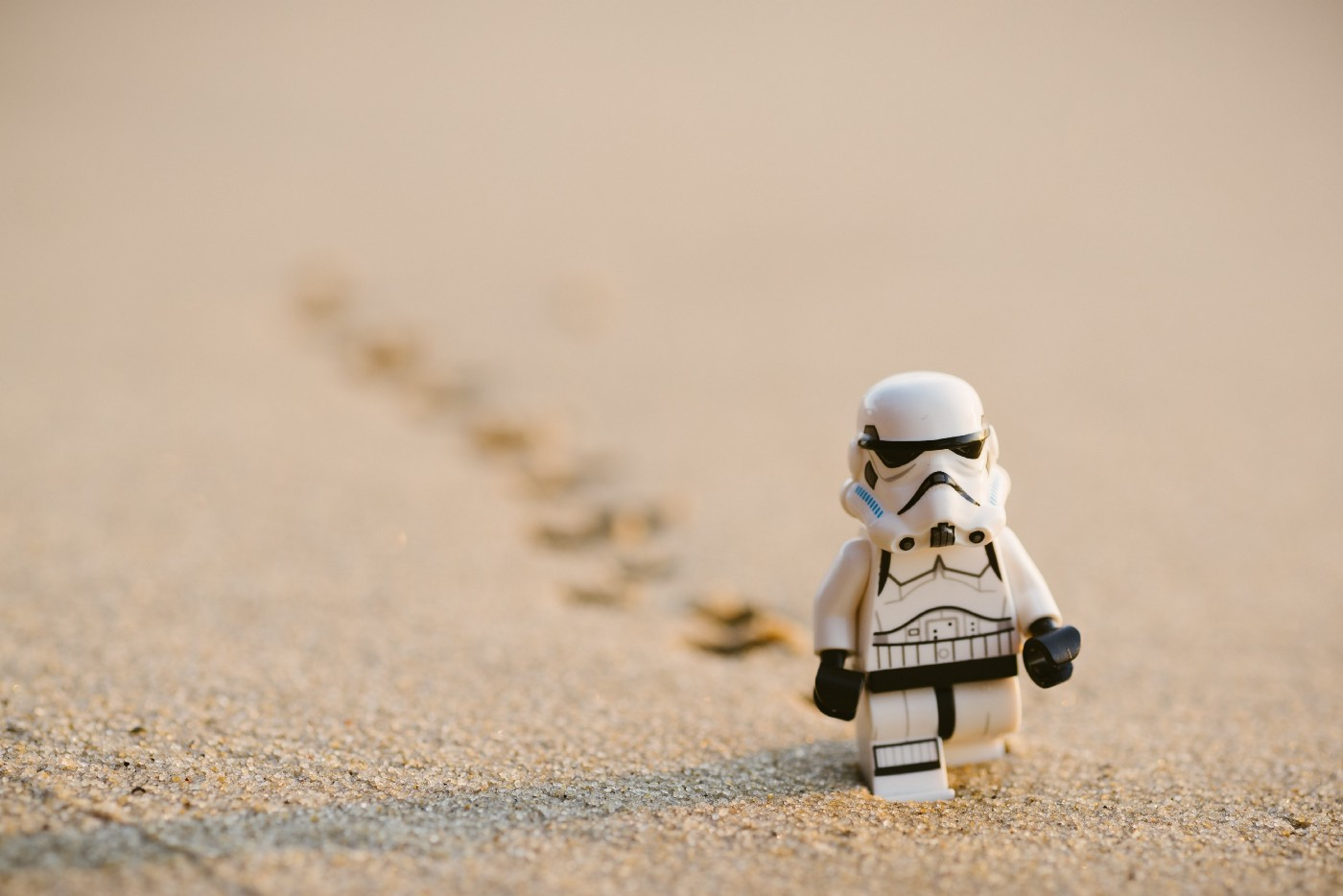 A tiny startrooper toy placed on the sand