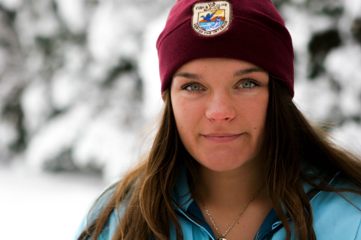 young woman in a snowy environment wearing a USFWS hat