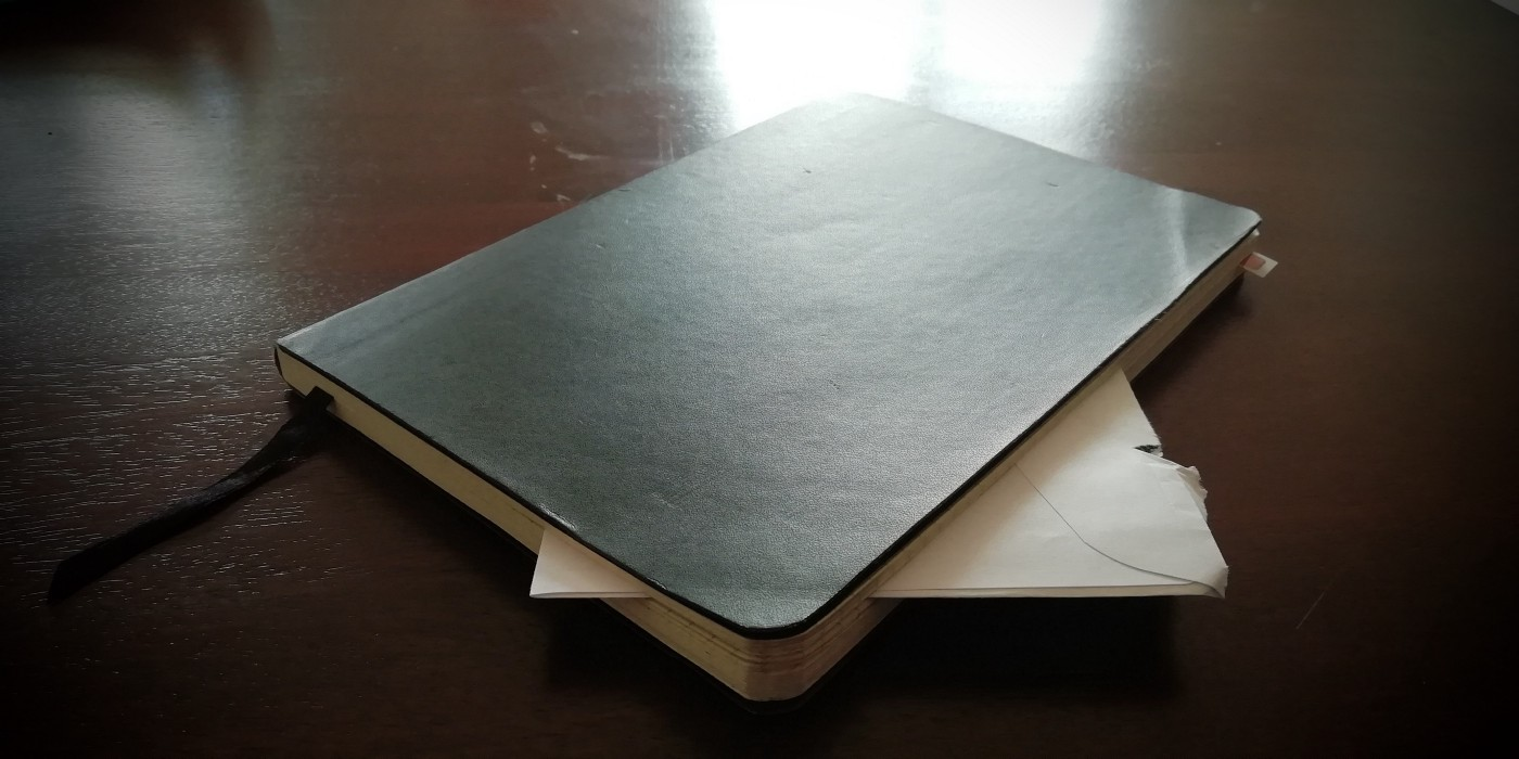 An image of white love letter envelope sneaking out of a black Moleskine book on an ebony table photographed by Anup Sam Ninan