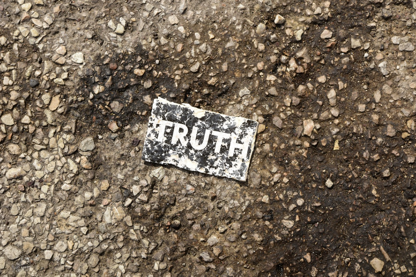Worn black piece of paper with white letters spelling TRUTH in a pothole on worn asphalt