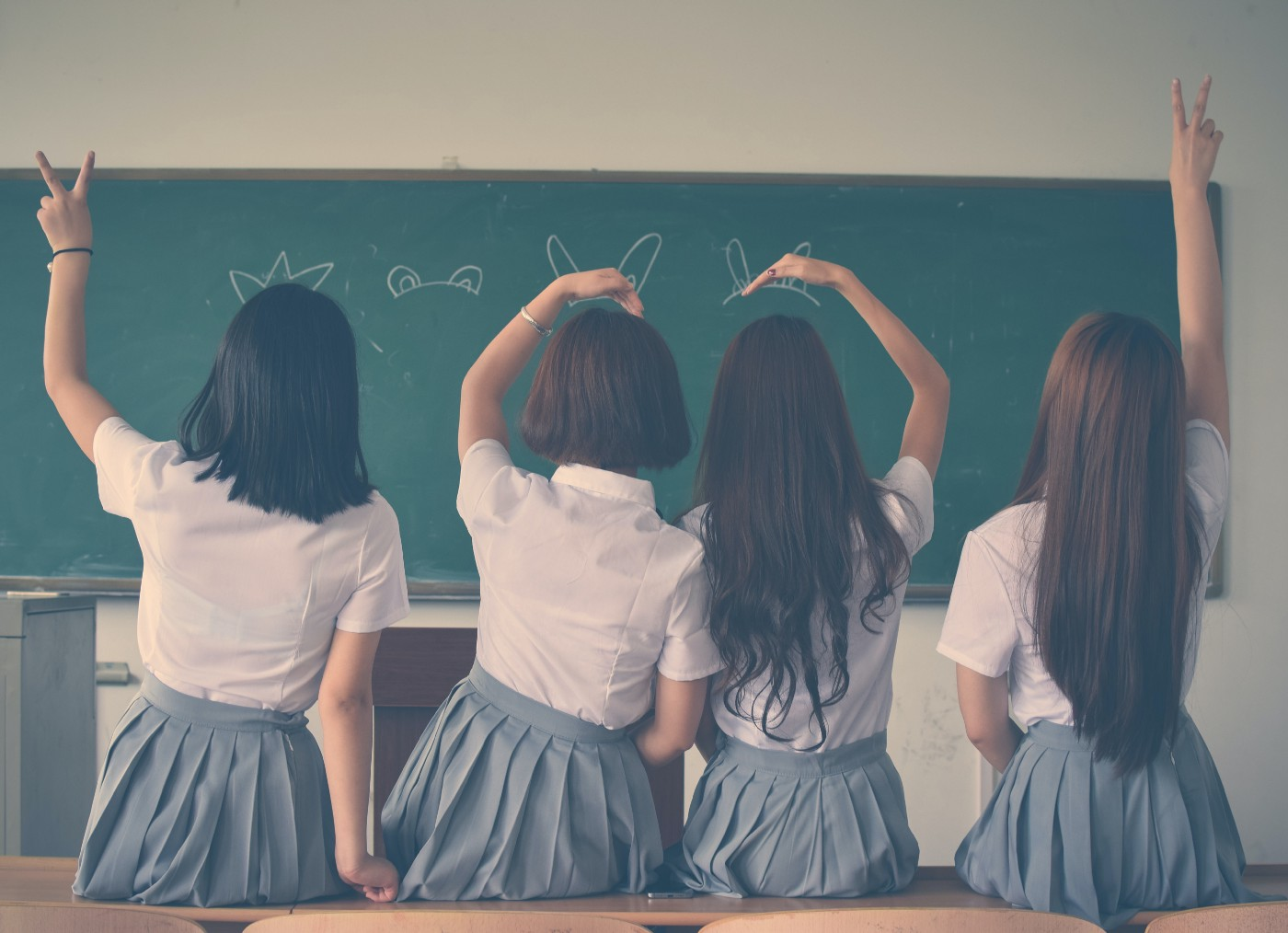 The backs of four girls in school uniform doing hand signs.