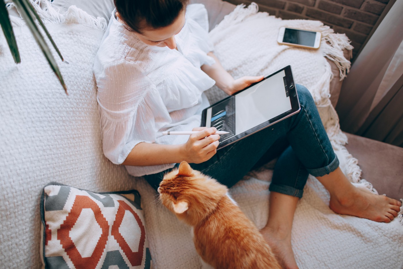Woman on the sofa with an orange tabby cat and her tablet computer