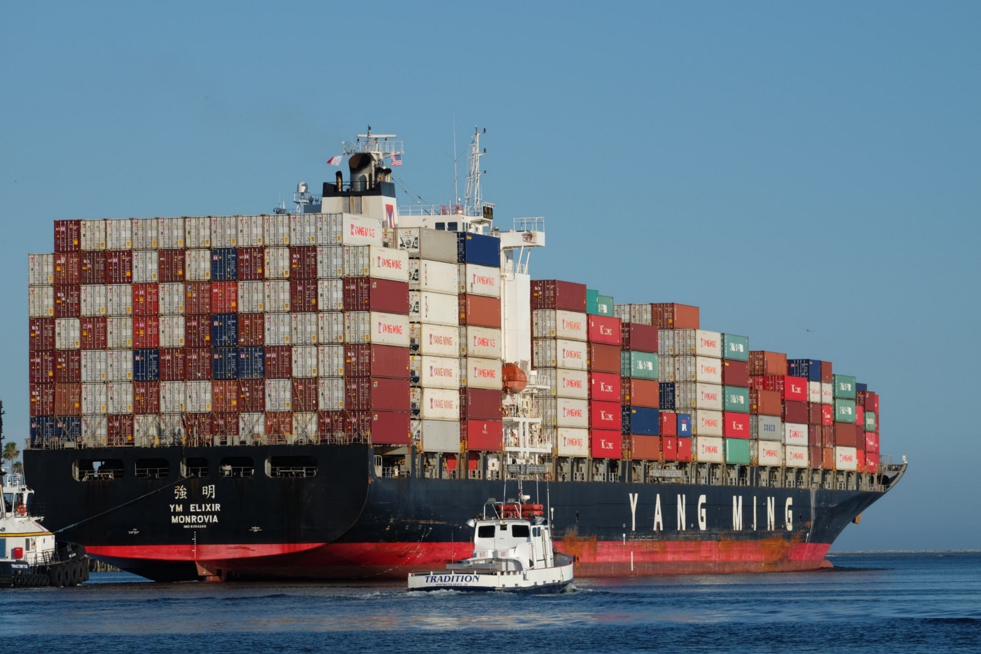 """A navy blue container ship with the words """"YANG MING"""" on the side."""