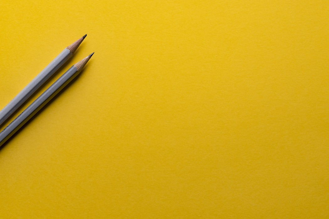 Two grey pencils atop a deep yellow background