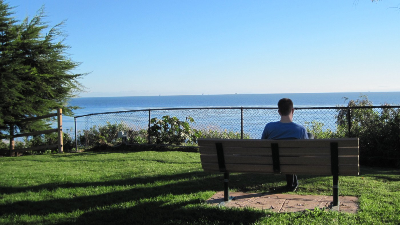 Man sitting on bench in Summerland, California, gazing thoughtfully at ocean