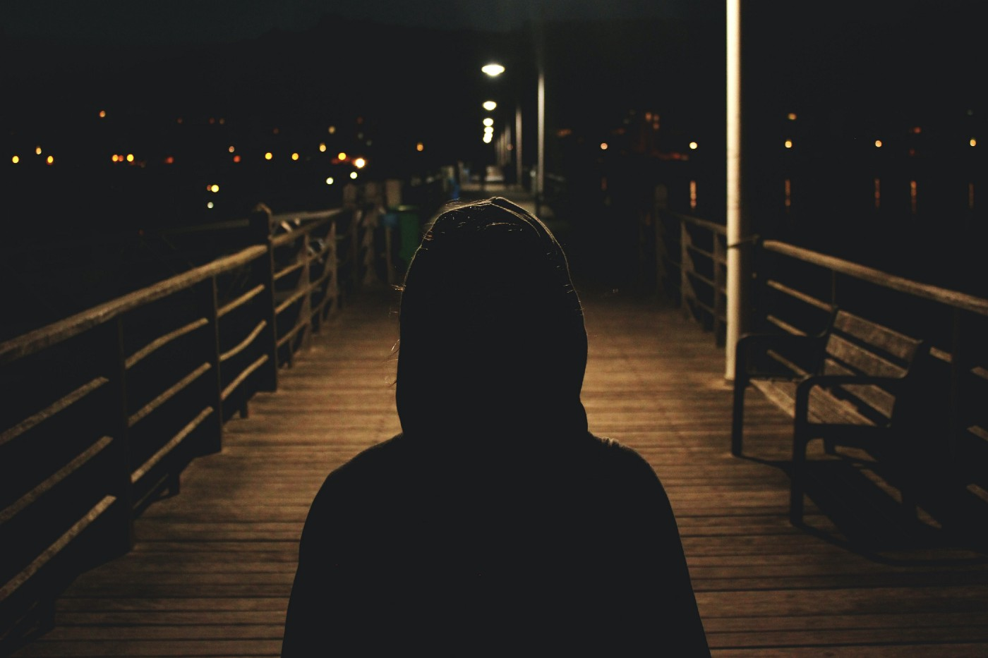 A person wearing a hoodie in a shadow, standing on a boardwalk at night.
