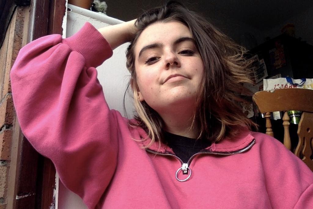 Pip, a white non-binary person with long hair swept over to one side and wearing a fluffy pink fleece, leans back and holds their head with a slight smile.
