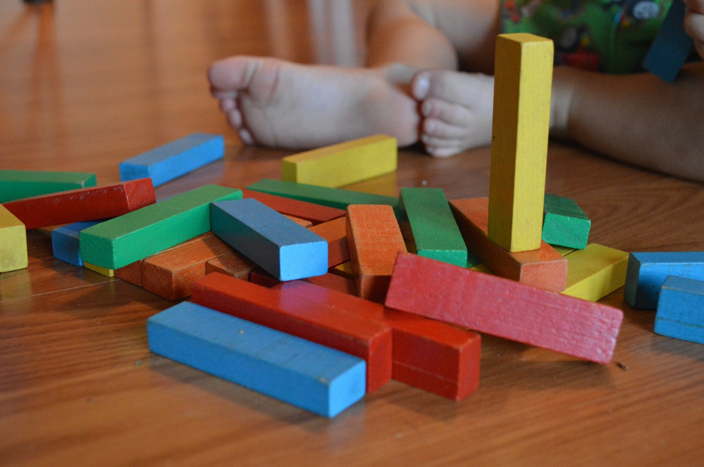 Colorful wooden blocks on floor, with baby feet in background