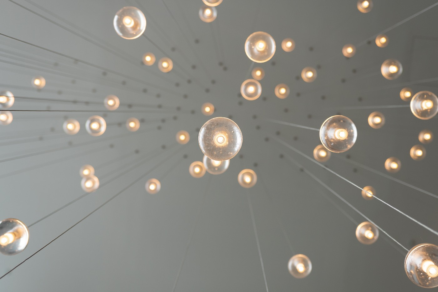 Photo of small light fixtures hanging from long wires as viewed from below.