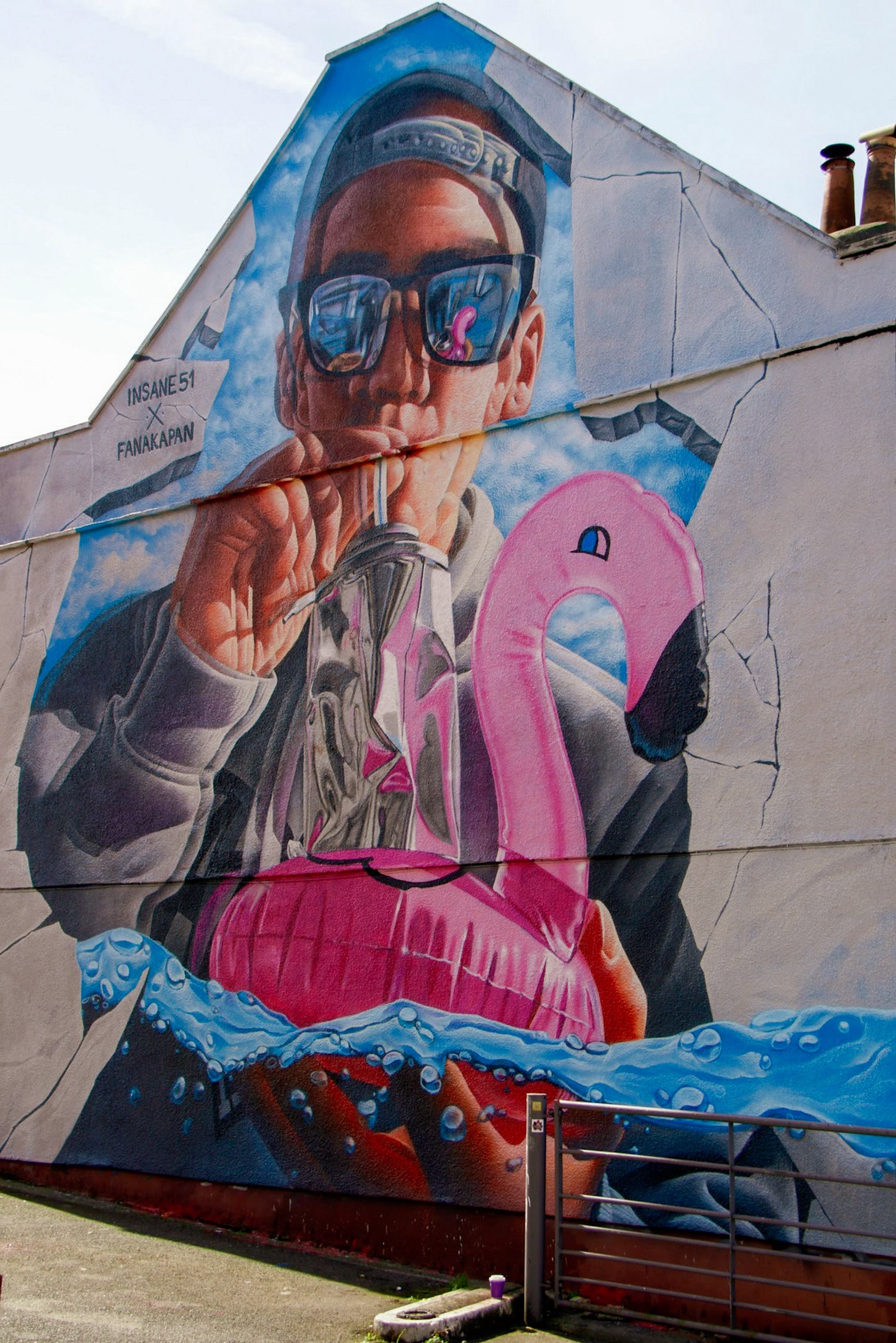 A mural of a man with sunglasses blowing up a pink inflatable flamingo.