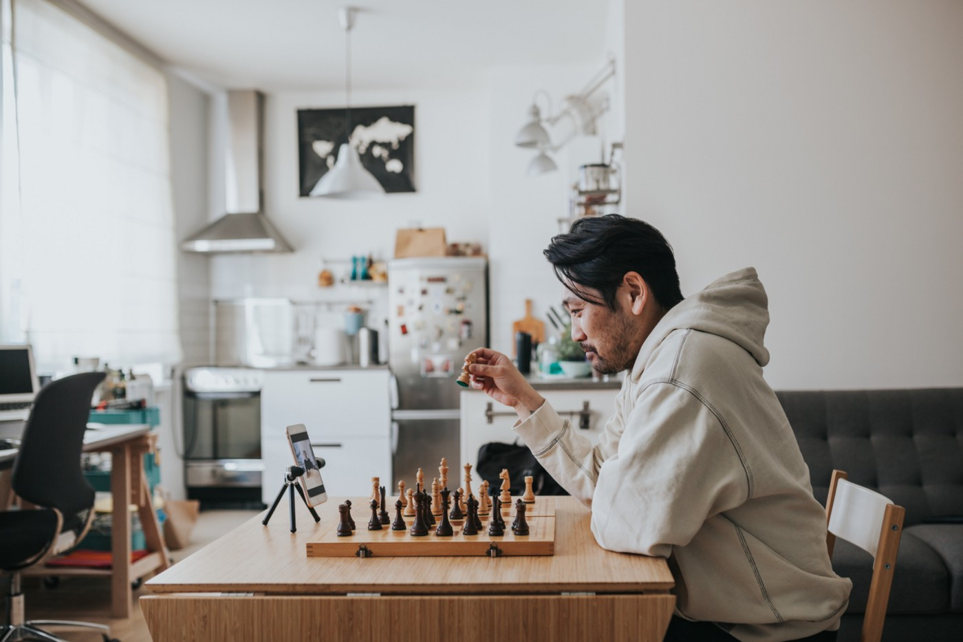 A man playing chess with a friend over a video call.