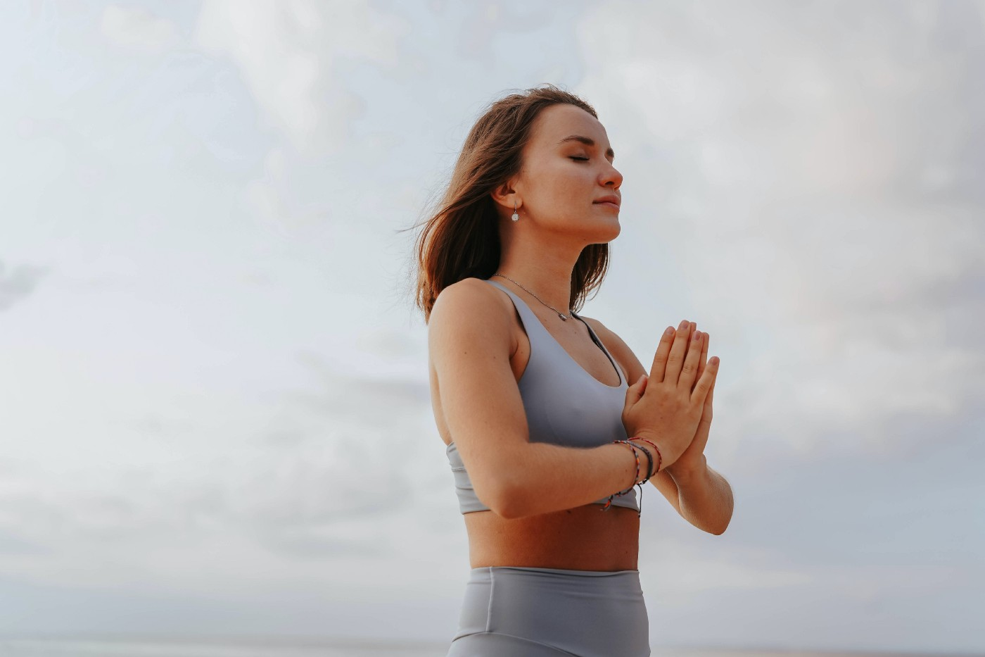 Woman meditating in front of open skies
