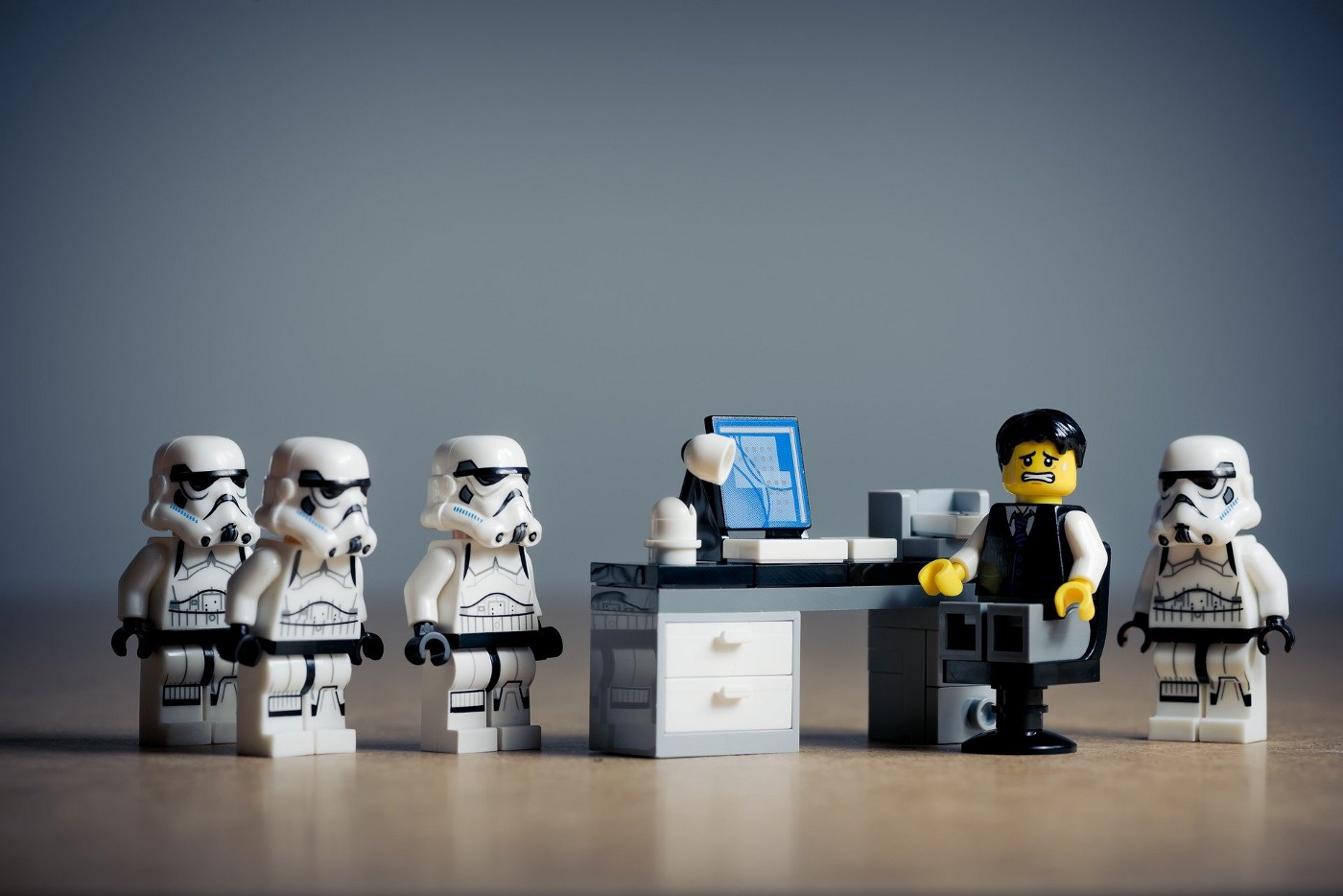 Lego figure in a suit at a desk surrounded by Lego storm troopers looking fearful