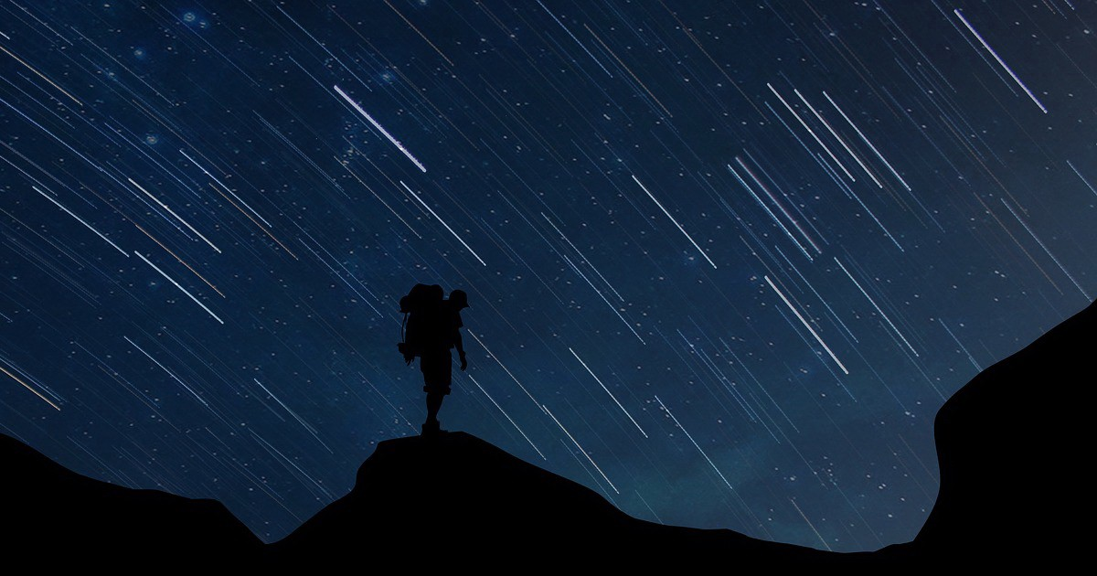 Man standing on hill at night with stars in the background.