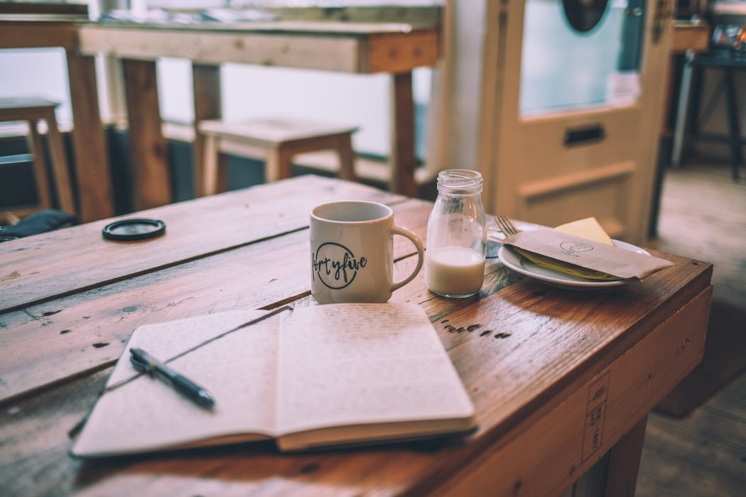 A wooden table with an open journal, mug, glass of milk, and a small plate on top.