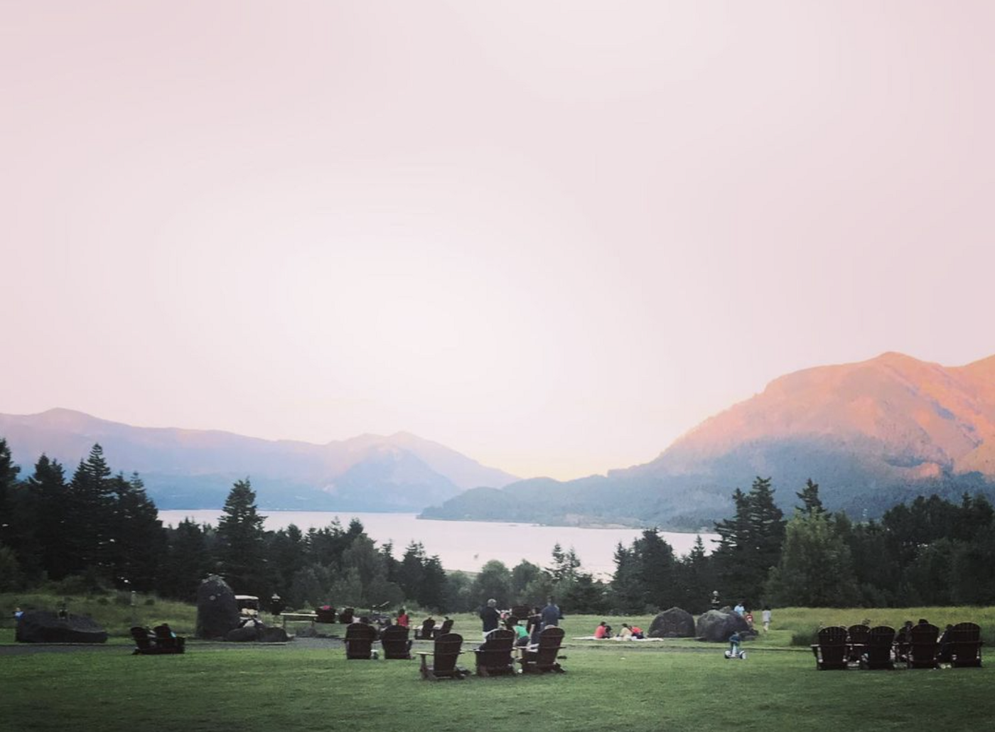 chairs on a grass hill overlooking river and surrounding hills in a pink dusk.