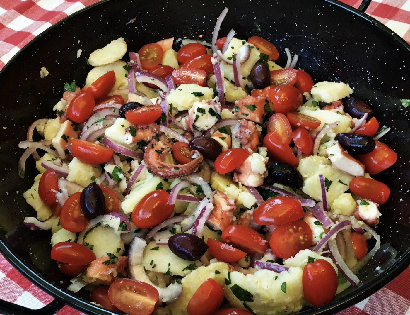 Octopus cut into small pieces and prepared with potatoes, tomatoes, and cucumbers.