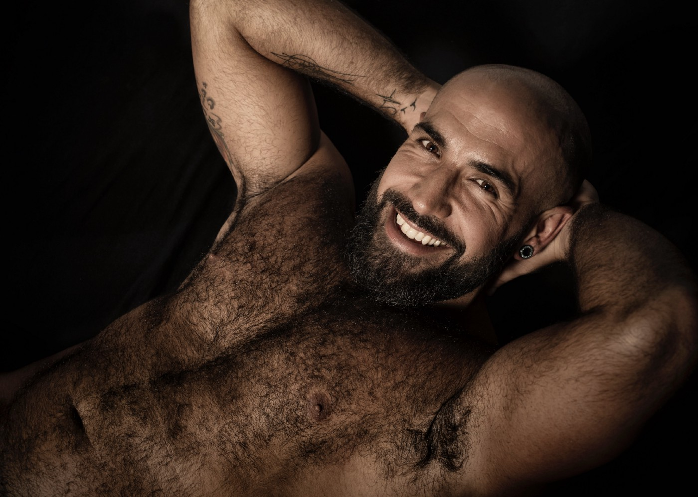 Handsome middle aged man with arms behind his head and no shirt on, smiling widely. Very hairy.