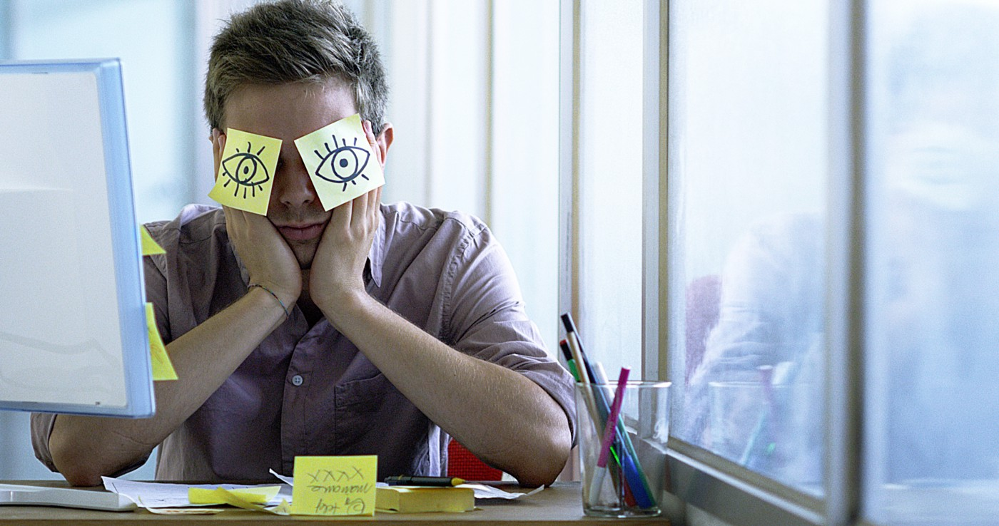A man sits at a desk with sticky notes that have eyes drawn on them covering his eyes.