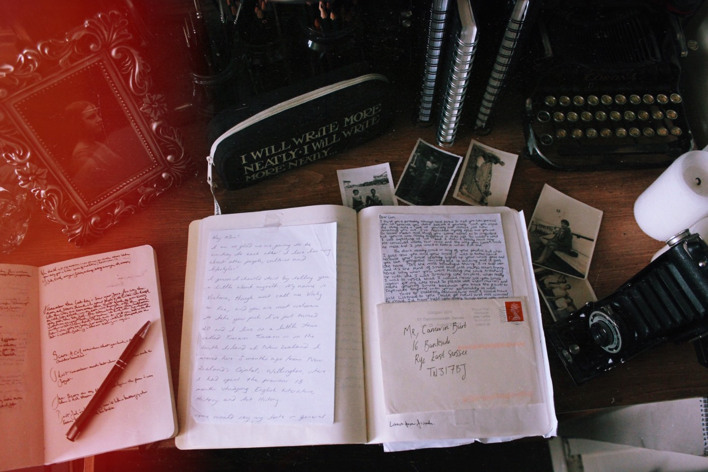 A desk with 2 notebooks, a framed photo, a typewriter, and a pencil bag. The photo has some light leak and looks vintage.