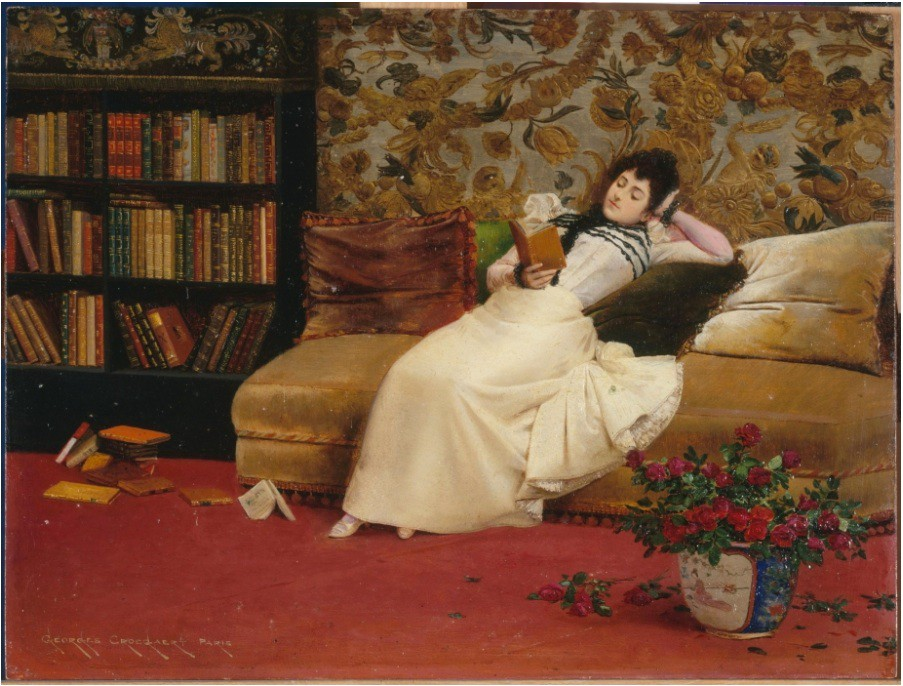 A woman in 19th century dress lounges on a chaise longue beside a bookcase and she is holding a book