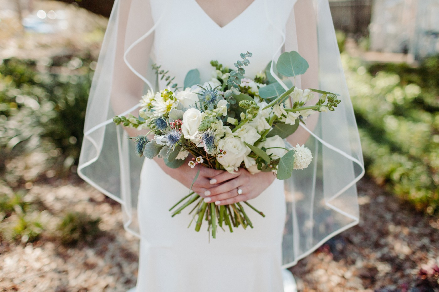 woman in wedding dress holding bouquet of white flowers and eucalyptus