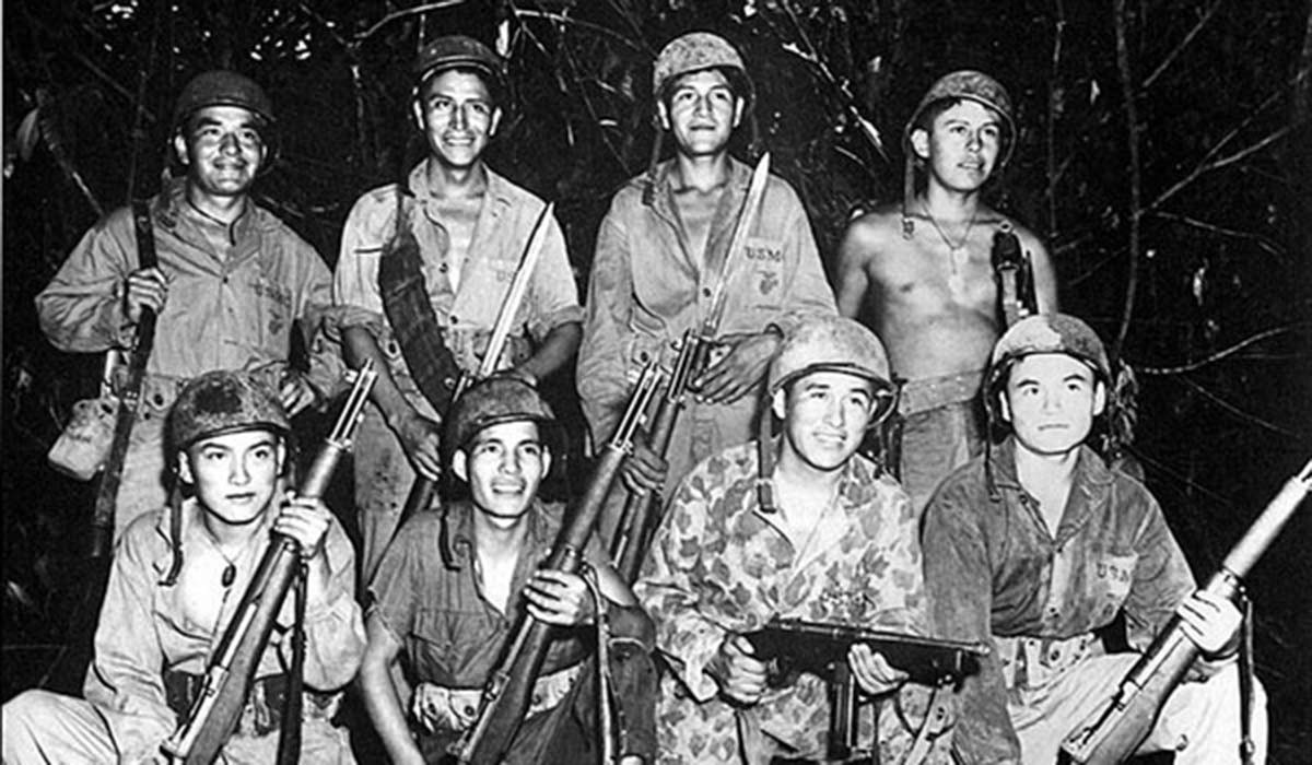Soldiers with weapons pose for a photo in the jungle