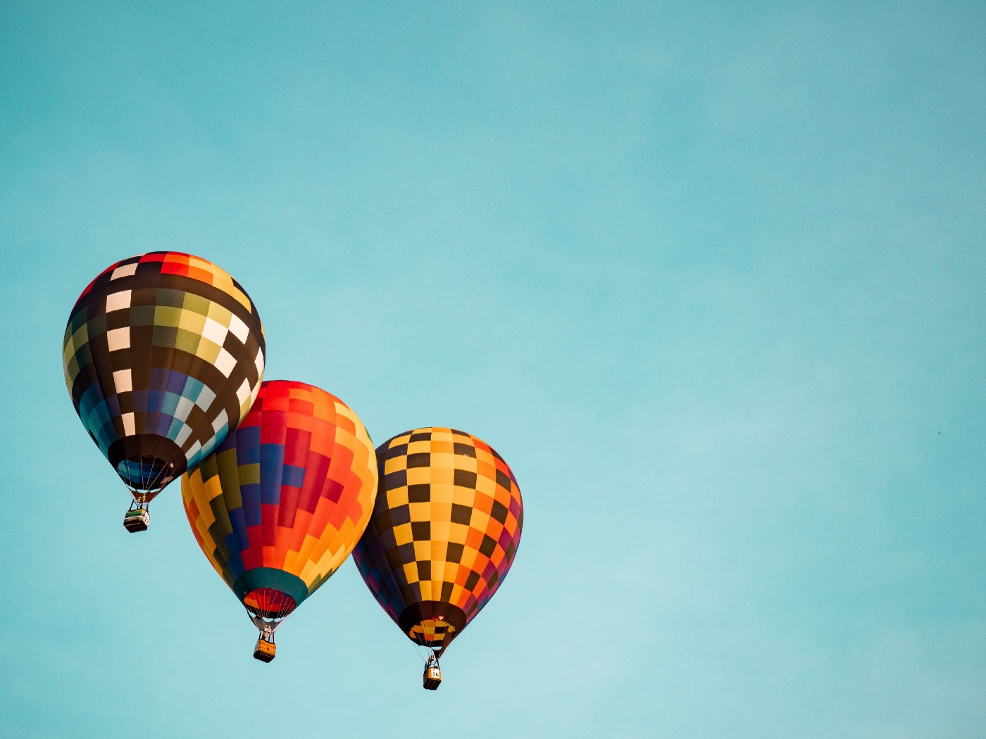 Three colorful hot air balloons floating against a blue sky