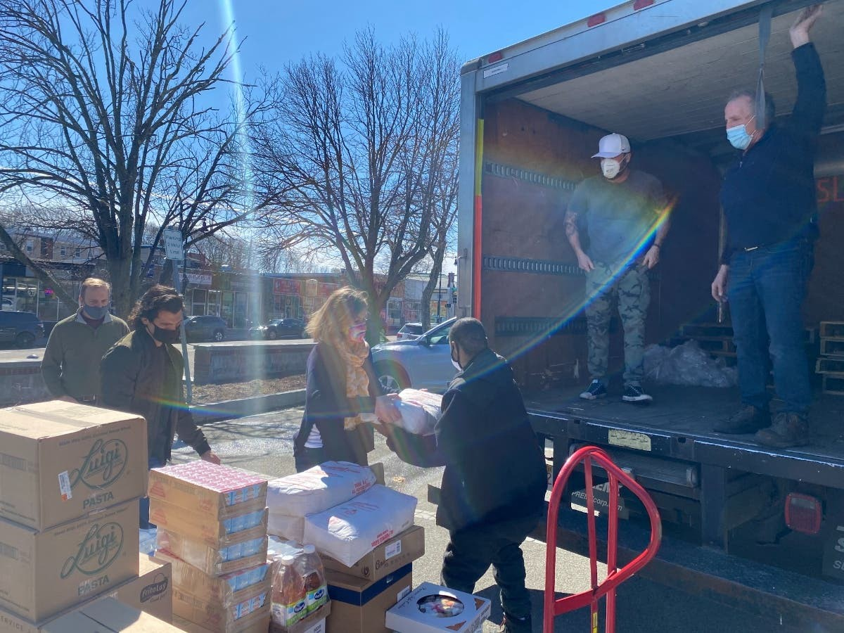 Volunteers load food donations on a truck