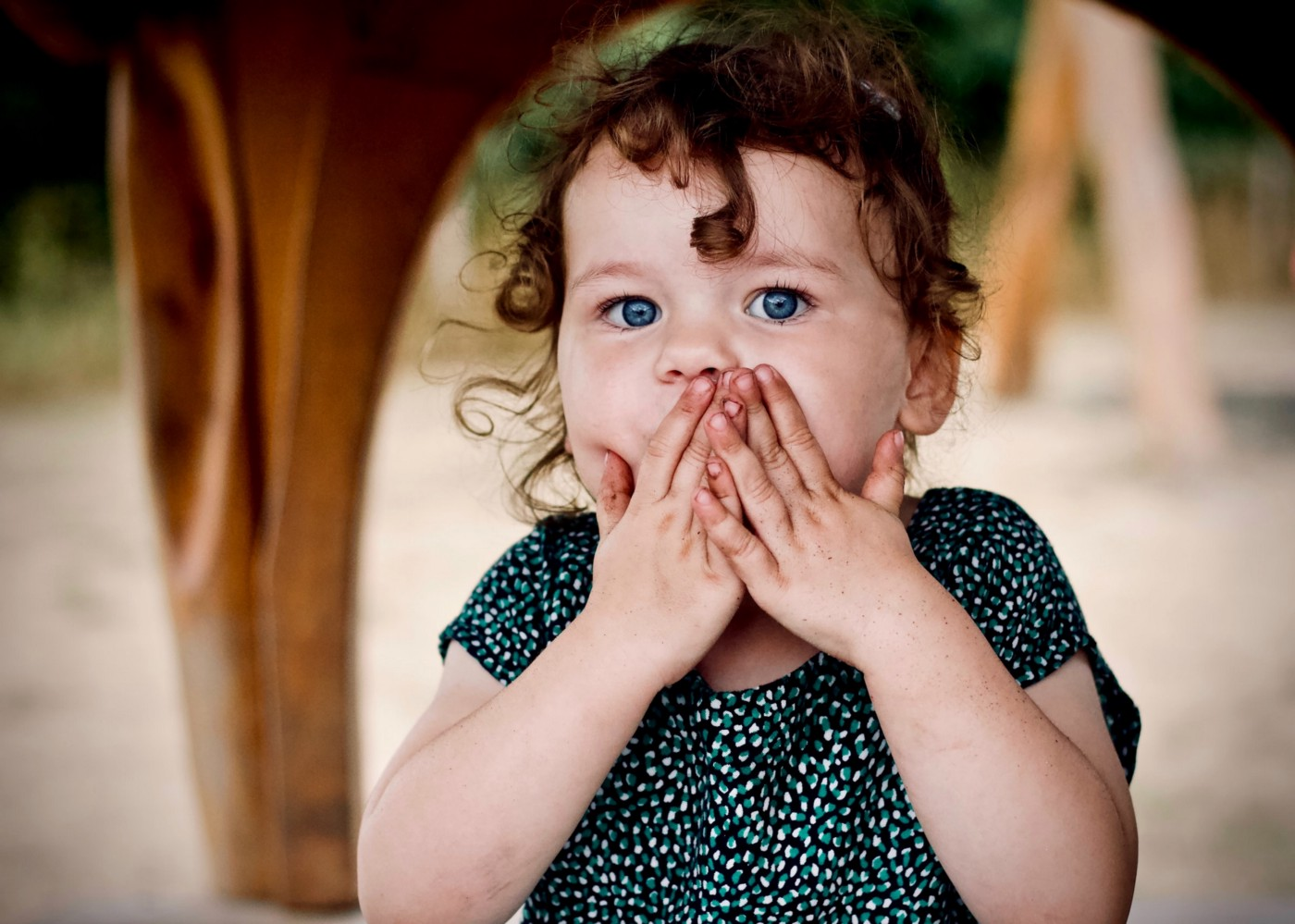 Little girl with hands over her mouth