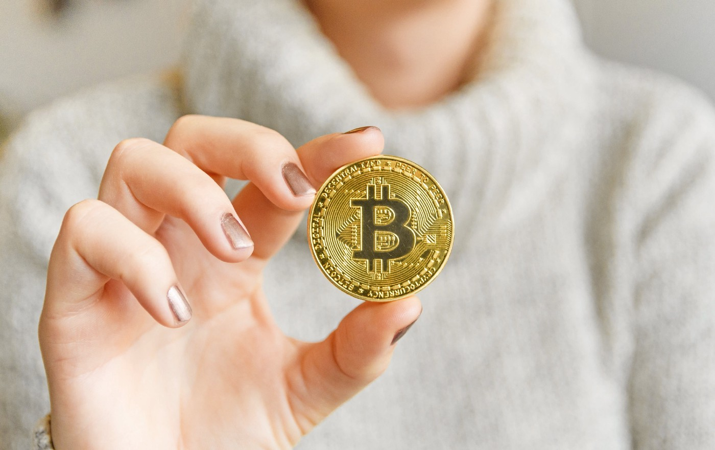 A person in a turtle neck holding a gold bitcoin.