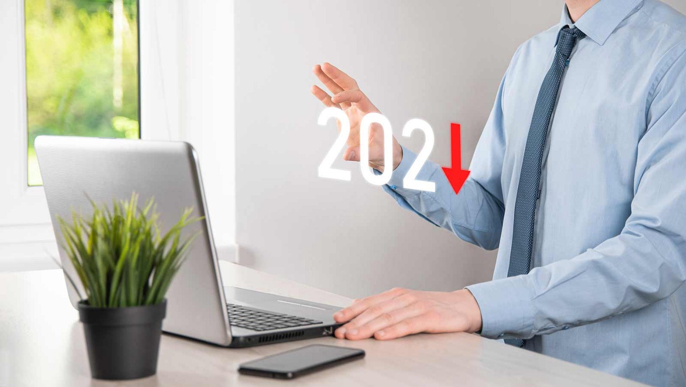 Businessperson using a laptop. The numbers 202 appear with a down arrow replacing the 1, indicating 'down in 2021.'