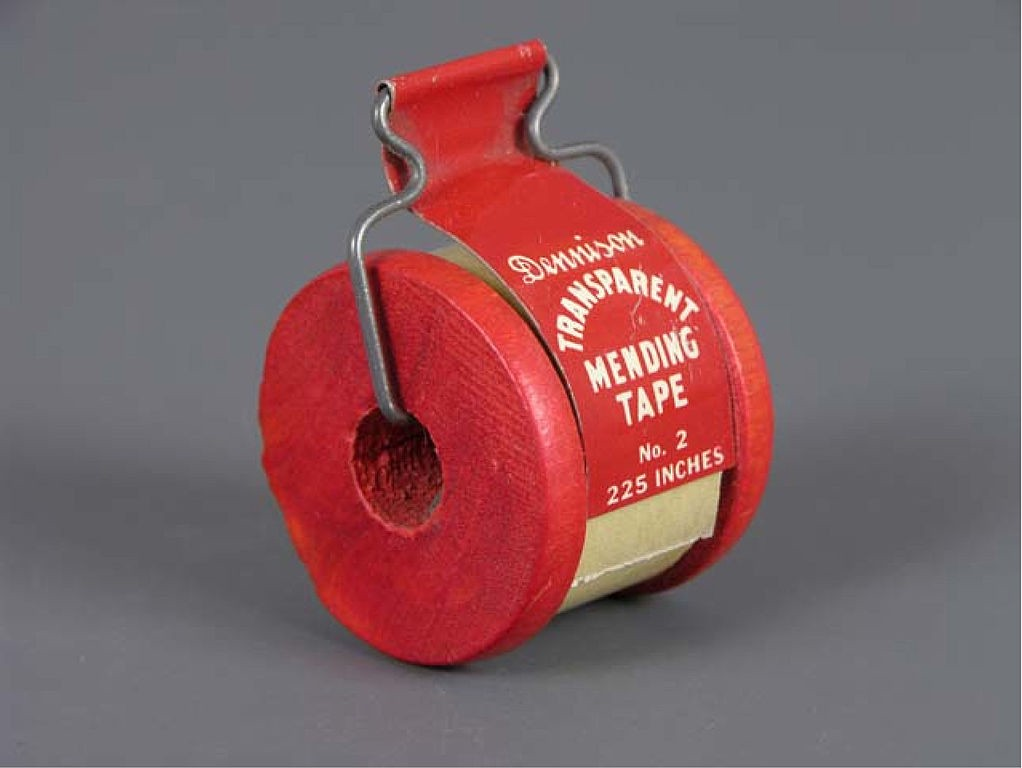 """A red tape dispenser with the brand name Dennison on it and a text""""Transparent Mending Tape"""" no 2"""